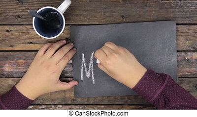 Top view. Man writes the word MENU with chalk on a blackboard.
