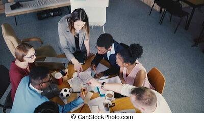 Top view multiethnic creative team brainstorming in trendy modern coworking office. Female boss leads the meeting 4K.