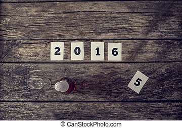 Top view of 2016 sign and a bottle of champagne with crystal glass on a textured rustic wooden desk