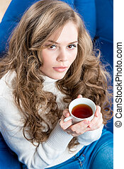 top view of a beautiful girl with a cup of tea on the couch