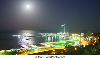 Top View of a Big City at Night, Ferris Wheel on the Background of the Sea and the Lunar Path. Traffic on the roads. Time Lapse