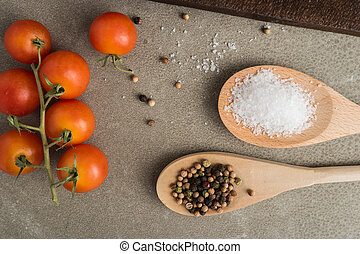 Top view of a bunch of natural cherry tomatoes, salt and pepper on cement background