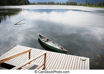 Top view of a canoe tied to a wooden dock