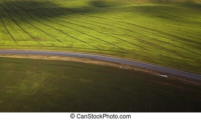 Top view of a car driving along a rural road between two fields