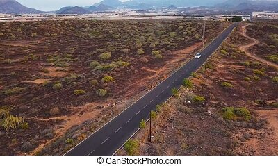 Top view of a car rides along a desert road