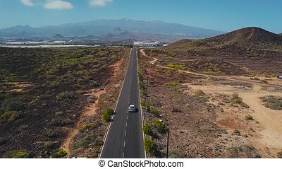 Top view of a car rides along a desert road on Tenerife, Canary Islands, Spain