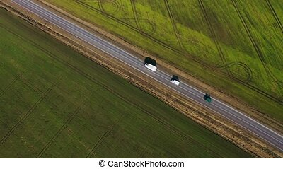 Top view of a cars driving along a rural road between two fields