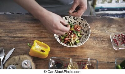 Top view of a chef mixing a vegetable salad in a plate