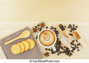 Top view of a cup of coffee with crackers and herbs on wood table.