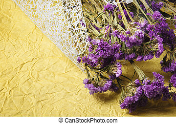 Top view of a cute bouquet of purple dried flowers on a bright yellow background. Yellow fabric with violet flowers, close-up.