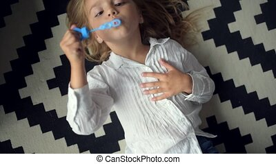 Top view of a cute little girl blowing soap bubbles