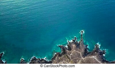 Top view of a deserted coast. Rocky shore of the island of Tenerife. Aerial drone footage of sea waves reaching shore