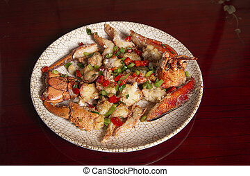 Top view of a dish of lobster with salt and pepper on a wooden table