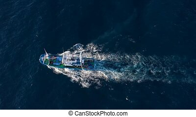 Top view of a fishing boat sailing in the Atlantic Ocean -...