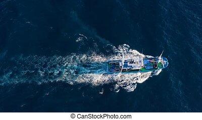 Top view of a fishing boat sailing in the Atlantic Ocean -...