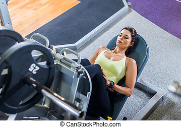 Top view of a fit young woman doing leg press in the gym