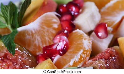 Top view of a fruit salad with mandarin, oranges, kiwi, pomegranate seeds, figs, banana and peaches