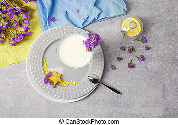 Top view of a glass bowl with milk, a plate, silver spoon and a yellow bright carambola on a light gray background.