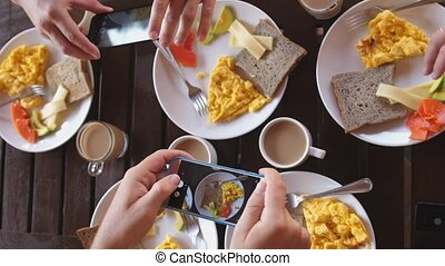 Top view of a group of friends having breakfast in a cafe at wooden table, taking picture of omelette, toasts and coffee with mobile phone. slow motion. 3840x2160