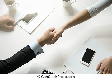 Top view of a handshake between man and woman