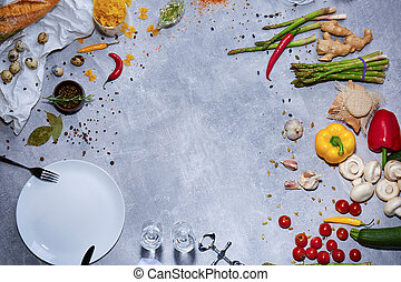 Top view of a kitchen table with chili pepper, asparagus, salad pepper, corkscrew, mushrooms, garlic on a gray background.