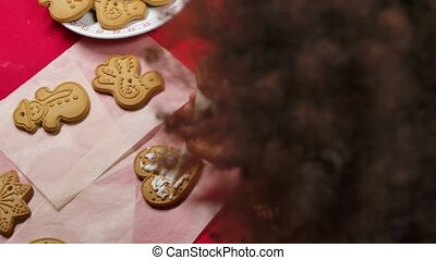 Top view of a little African American girl in a New Years print sweater decorates a traditional Christmas cookie with icing. Close up. Slow motion.