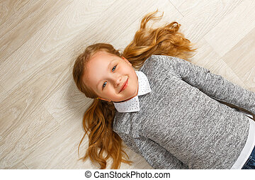 Top view of a little girl lying on the floor