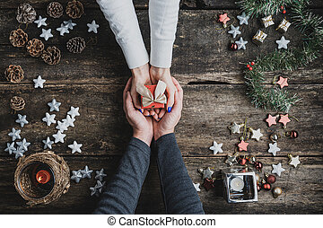 Top view of a male hands cupping female hands holding small red holiday gift box