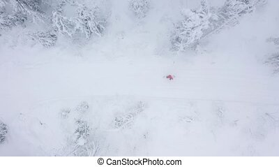 Top view of a man who snowboarding down a mountainside among...