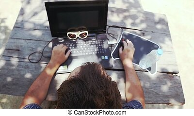 Top view of a man working on his laptop by wooden table next to bottle of water and sunglasses. Writing Down Stuff in his Notebook. slow motion.