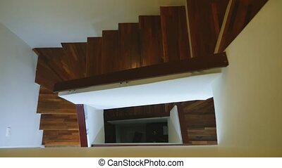 top view of a modern staircase with brown wooden steps and white walls. three flights of stairs.