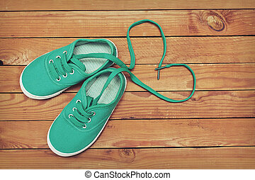 Top view of a pair of shoes with laces making heart shape on...