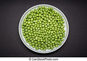 Top view of a plate with fresh Green pea isolated on black ...