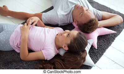 Top view of a positive little girl resting on the floor with her father