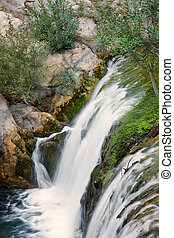 Top view of a small waterfall on a river in summer
