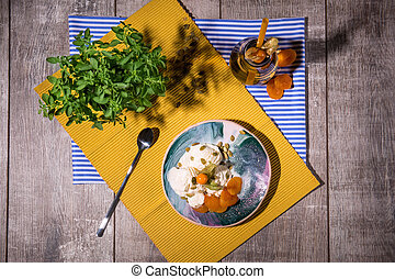 Top view of a summer breakfast. White ice cream, green foliage, jar of fruity drink on a table background. Light snacks.