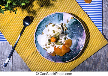 Top view of a summer breakfast. White ice cream with apricots and a spoon on a bright fabric background. Cold snacks.