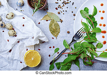 Top view of a table with bay leaves, green salad leaves, quail eggs, a half of lemon on a light gray background.