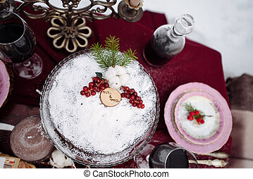 Top view of a table with dread and cookies baskets candles, two chairs covered white fur on the background. Picnic in the winter forest