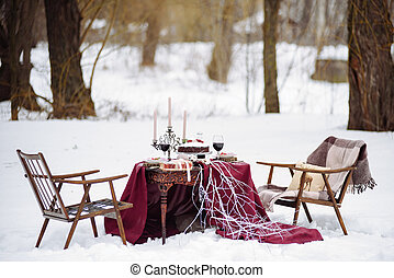 Top view of a table with dread and cookies baskets candles, two chairs covered white snow on the background.