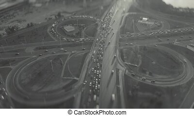 Top view of a traffic intersection, at rush hour, black and white video with tilt shift effect