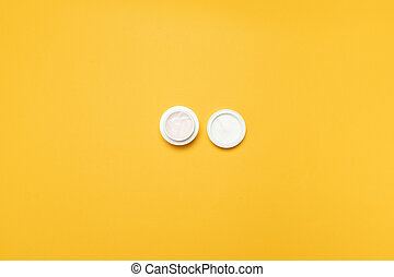 Top view of a white plastic jar with face cream. Nursing care for body skin
