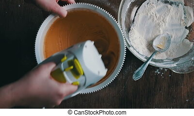 Top view of a woman chef who mixes dough electric mixer, Mixing dough with electric mixer. Cooking at home.