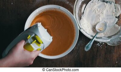 Top view of a woman chef who mixes dough electric mixer, Mixing dough with electric mixer. Cooking at home. Accelerated video