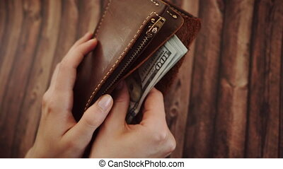 Top view of a woman counting and Takes out dollars from her brown leather wallet. Female holds purse against wooden background. Slow motion