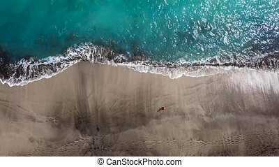 Top view of a woman in red dress walking barefoot along wet sand ocean beach