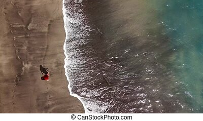 Top view of a woman in red dress walking barefoot along wet sand ocean beach
