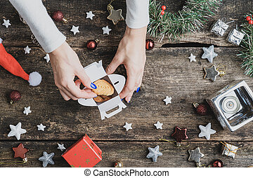 Top view of a woman placing holiday cookies in mini gift box
