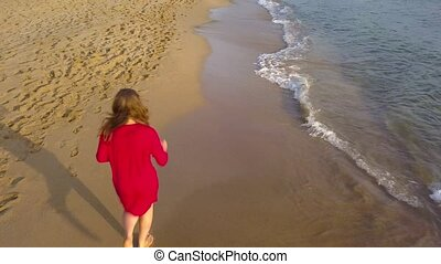 Top view of a woman running barefoot along wet sand beach. Running wave is washing away footprints on the sand