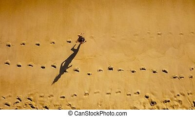 Top view of a woman running barefoot along wet sand ocean beach